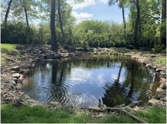 Плавательное озеро в лесной местности с декоративным водопадом с. Романьков